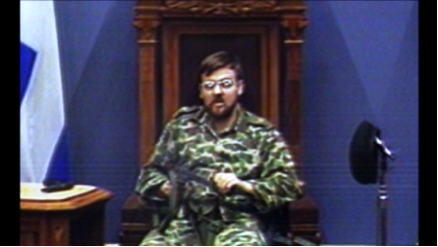 1: Denis Lortie, armed with a submachine gun, sits in the President's chair in the Blue Chamber at the Quebec National Assembly.